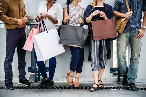 Un grupo de cinco personas con bolsas de compras de moda